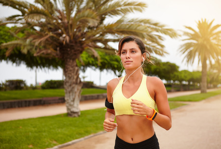 waist up: Waist up portrait of a young runner listening to music while doing sport outside