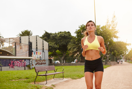 Three quarter length portrait of a young female running outside for healthy living
