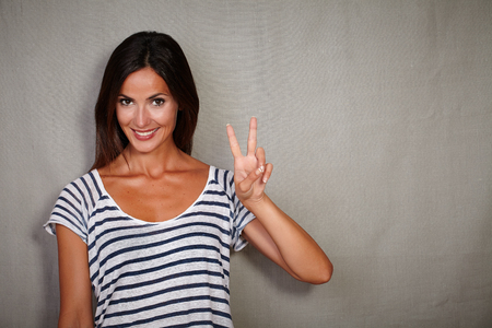 caucasian ethnicity: Happy young lady of caucasian ethnicity celebrating with victory sign