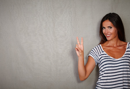 victory sign: Good-looking woman celebrating with victory sign while standing - copy space