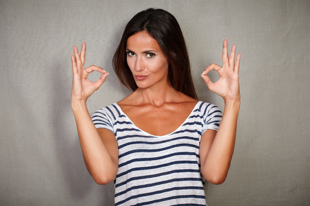 confidence: Confident woman in blue blouse congratulating with ok sign