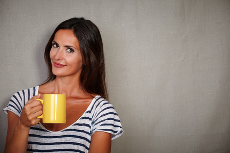 waist up: Waist up portrait of a brunette lady holding mug while looking at camera - copy space