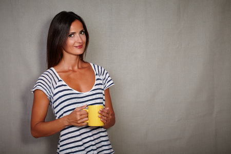 goodlooking: Good-looking brunette female in blue blouse holding coffee cup - copy space