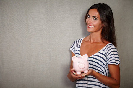 charismatic: Charismatic lady in casual clothing holding moneybox while smiling - copy space Stock Photo
