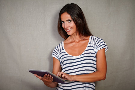goodlooking: Waist up portrait of a good-looking female using tablet while standing - copy space