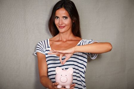 save: Waist up portrait of a happy woman in her 30s holding a piggy bank with savings Stock Photo