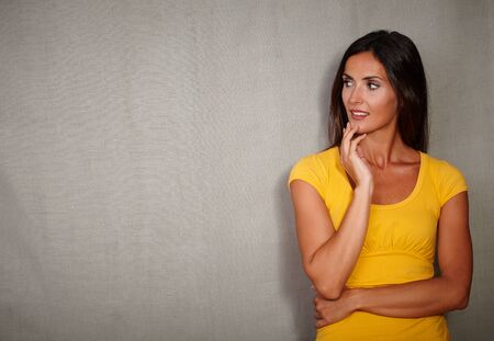 contemplative: Contemplative woman in yellow blouse thinking while looking away - copy space Stock Photo