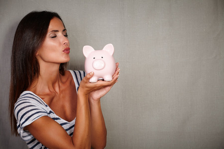 charismatic: Charismatic young woman in her 30s kissing a piggy bank with eyes closed