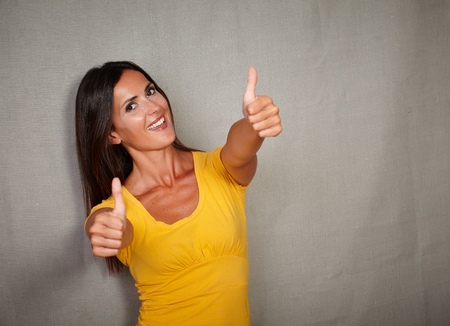 congratulating: Happy woman in yellow tank top congratulating with thumbs up - copy space