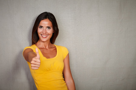congratulating: Good-looking woman in yellow blouse congratulating with thumb up
