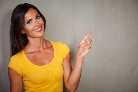 crossing fingers: Charismatic woman in tank top crossing fingers while smiling - grey texture background