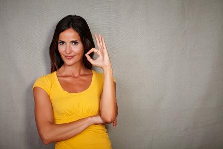 caucasian ethnicity: Confident woman of caucasian ethnicity congratulating with ok sign