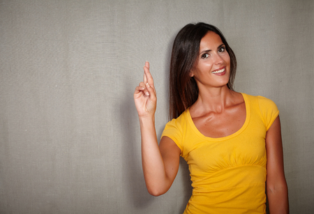 caucasian ethnicity: Confident youngster of caucasian ethnicity crossing fingers while smiling Stock Photo