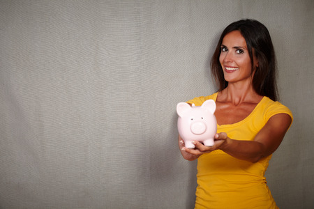 30s: Happy young woman in her 30s holding piggy bank while looking at camera - copy space