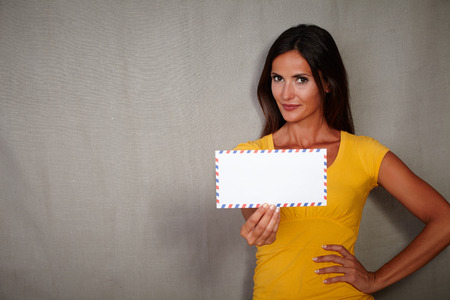 caucasian ethnicity: Confident woman of caucasian ethnicity holding mail while standing - copy space Stock Photo