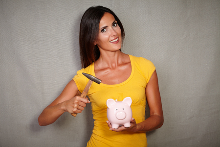 tank top: Good-looking lady in yellow tank top breaking piggy bank with hammer