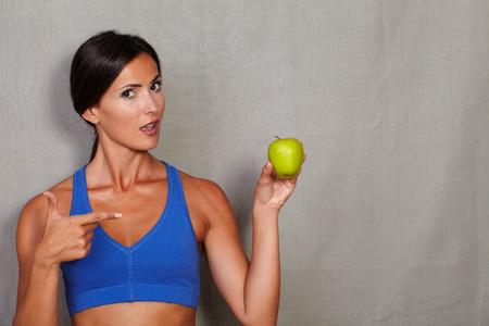 an open mouth: De pie mujer apuntando a la manzana con la boca abierta contra el gris de textura de fondo Foto de archivo