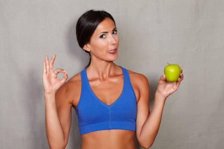 caucasian ethnicity: Caucasian ethnicity woman showing ok sign and licking his lips while holding apple against grey texture background
