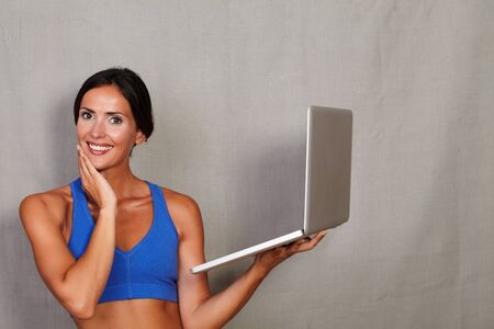 sport wear: Happy female with hand on chin and holding laptop while looking at camera in sport wear against gray texture background