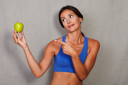 charisma: Smiling woman holding and pointing to apple against grey texture background