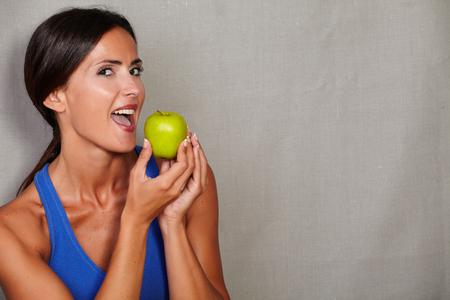 an open mouth: Hembra adulta con la boca abierta que sostiene la manzana y mirando a la c�mara sobre fondo gris de la textura Foto de archivo