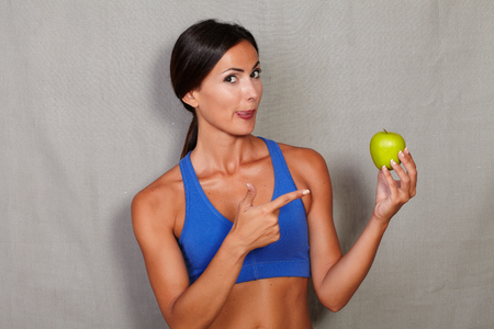 sport wear: Fitness woman licking his lips and pointing to apple in sport wear against grey texture background