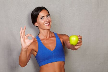 ok sign: Satisfied lady showing apple and ok sign in fitness sport wear on grey texture background Stock Photo