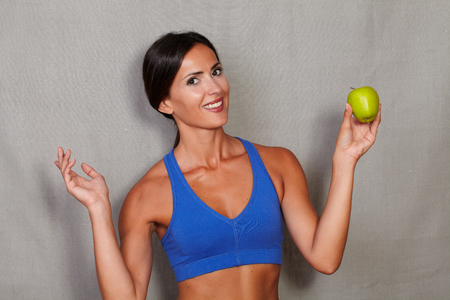 charisma: Smiling lady holding apple and looking at camera with toothy smile and standing against grey texture background