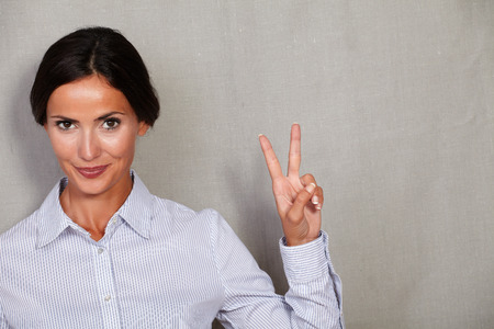 welldressed: Well-dressed adult female showing victory sign and looking at camera in formal clothing on grey texture background