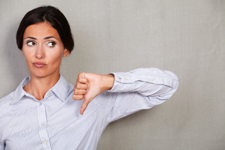 Unhappy businesswoman with thumb down looking away unsatisfied on grey texture background - copy space