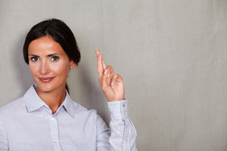 formal clothing: Long hair businesswoman crossing her fingers with hair back and formal clothing on grey texture background Stock Photo