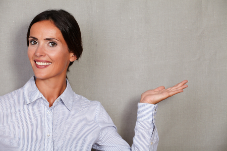 toothy smile: Toothy smile businesswoman holding left palm up in button down shirt while looking at camera on grey texture background