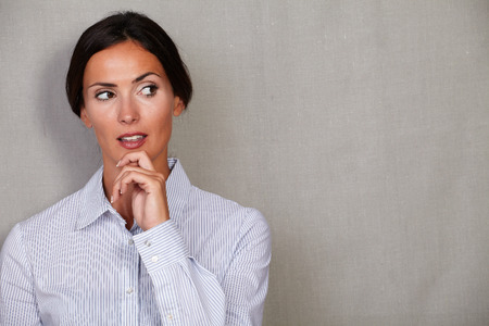 button down shirt: Reflective businesswoman in button down shirt with hand on chin while looking away on grey texture background
