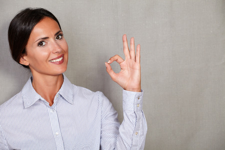 perfect sign: Straight hair female smiling with perfect sign gesture while looking at camera in formal wear on grey texture background