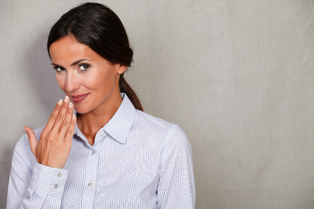 formal clothing: Smiling businesswoman with hand to her mouth in formal clothing while looking at camera on grey texture background