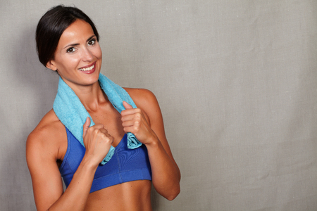 charismatic: Charismatic fitness female with towel on neck wearing tank top and smiling while looking at camera on grey texture background