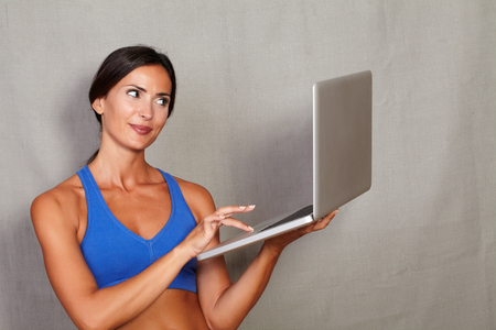 sport wear: Smiling brunette female holding and using laptop while standing in sport wear on grey texture background