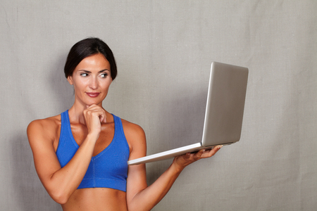 sport wear: Adult long hair female in sport wear holding laptop computer and wondering with hand on chin against grey texture background