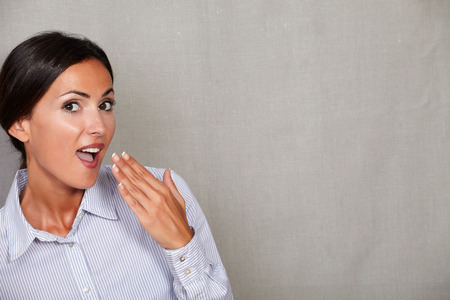 formal clothing: Caucasian ethnicity woman with hand to mouth gesture in formal clothing and looking at camera on grey texture background Stock Photo