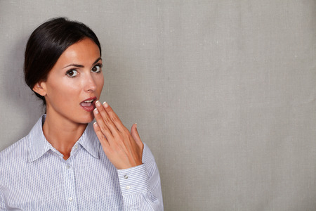 formal clothing: Surprised female in formal clothing with hand to mouth gesture shocked and looking at camera on grey texture background