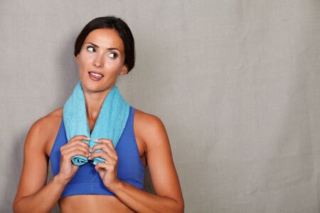 distrustful: Open mouth lady with towel on neck looking away in sport wear on grey texture background - copy space