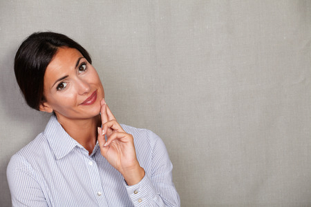 formal clothing: Smiling lady in formal clothing crossing her fingers and expecting while looking at camera on grey texture background