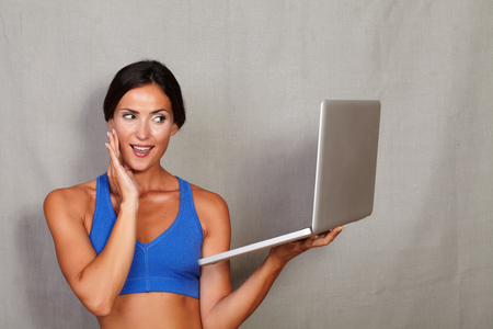 toothy smile: Impressed lady with hand on face and toothy smile while holding laptop in fitness gym clothing on grey texture background