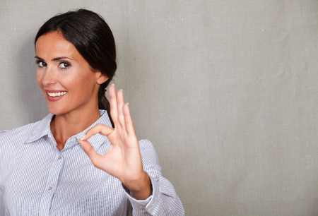 perfect sign: Excited businesswoman smiling and showing perfect sign while looking at camera on grey texture background Stock Photo