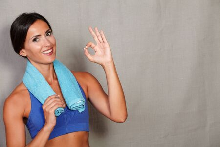 toothy smile: Satisfied fitness lady showing ok sign and toothy smile with towel on neck against grey texture background