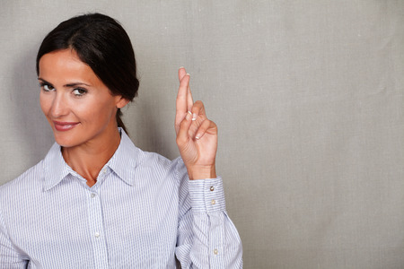 crossing fingers: Young adult female in button down shirt wishing and crossing fingers while looking at camera against grey texture background