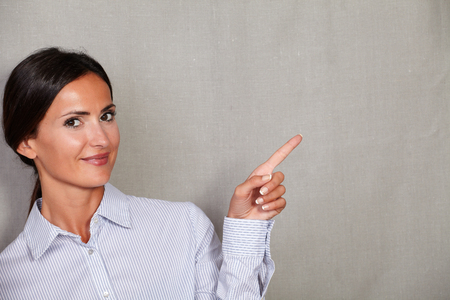 attractiveness: Well-dressed adult lady smiling and pointing to her left while looking at camera on grey texture background