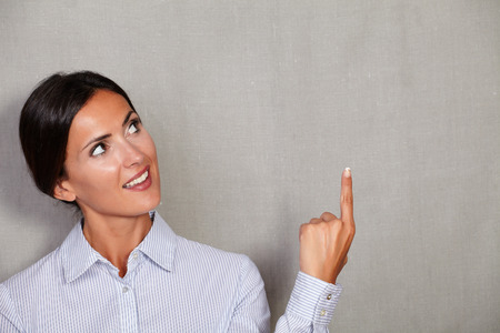 caucasian ethnicity: Caucasian ethnicity female pointing up while smiling and looking away in formal clothing against grey texture background - copy space