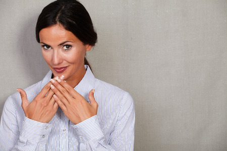 formal clothing: Caucasian ethnicity businesswoman with hands to her mouth in formal clothing while looking at camera on grey texture background