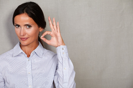 formal clothing: Well-dressed female with ok sign gesture and looking at camera in formal clothing against grey texture background
